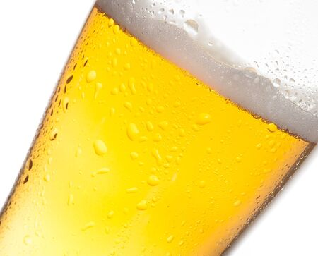 tilted: detail of tilted glass of fresh beer with drops on white background, with space for text