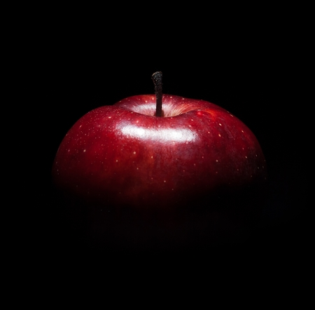 fresh red apple against black background with space for text