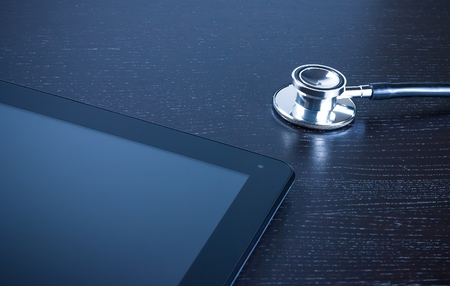 medical stethoscope on modern digital tablet pc on wood\ table. Concept of new technology for research