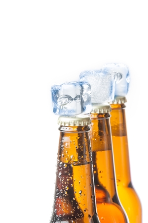 three bottle of fresh beer with ice on top and drops,concept of fresh beer on summer, on white background photo