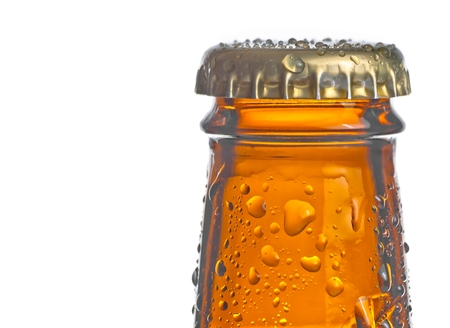 closeup of a top of bottle of fresh beer with drops with space for text on white background photo