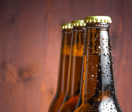 three bottle of fresh beer with drops on wood background photo