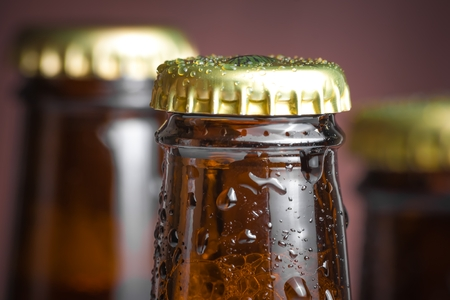 closeup of top of bottle of fresh beer with drops, with space for text on wood background photo