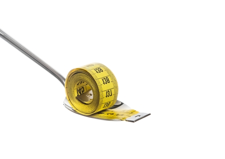 measuring tape on spoon, concept of nutrition and diet on white with space for text photo