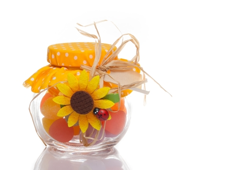 colourful multi coloured candy in a decorative glass jar for a festive gift on white  photo