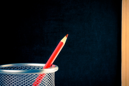back to school, red pencil in container against empty blackboard for text  photo