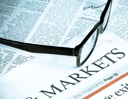 black eye glasses near word markets on financial newspaper, business and finance concept photo