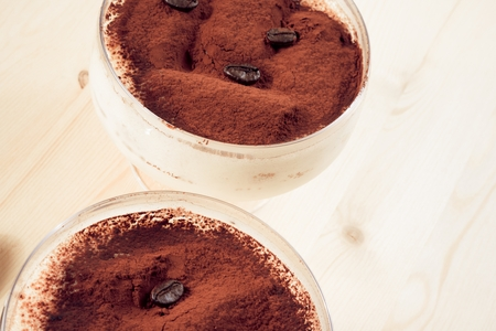 close-up of italian tiramisu dessert served in a cup with coffee beans photo