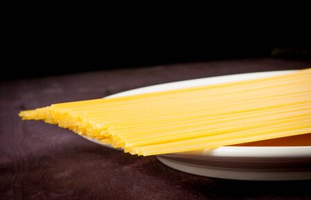 raw pasta spaghetti on flat over wood table with space for text, typical italian cuisine photo
