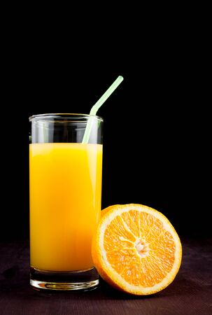 full glass of orange juice with straw near half orange on\ black background and space for text