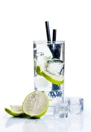 Cocktail with ice and lime slice isolated on white background photo