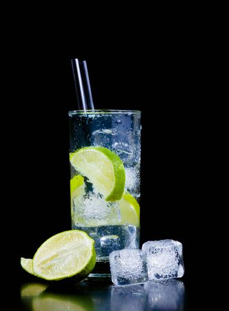 Cocktail with ice and lime slice with straw on black background and space for text photo