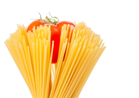 raw pasta spaghetti with tomato inside on white background with space for text, typical italian cuisine photo