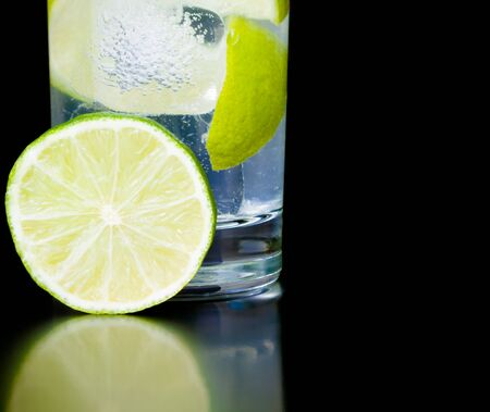 lime slice near cocktail on black background and space for text photo