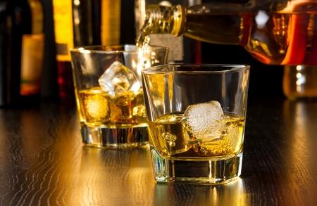 botella de whisky: camarero vierte el whisky detrás de un vidrio de whisky en la mesa de madera