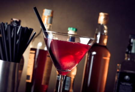red cocktail into a glass with ice and  ice straw in front of bottles Stockfoto