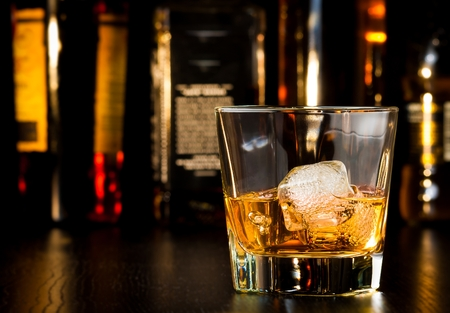 whiskey glass with ice in front of bottles on wood table