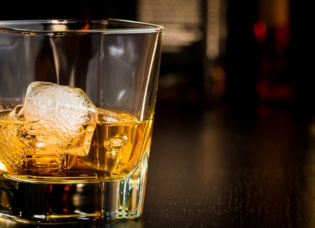 whiskey glass with ice in front of bottles on wood table with space for text photo