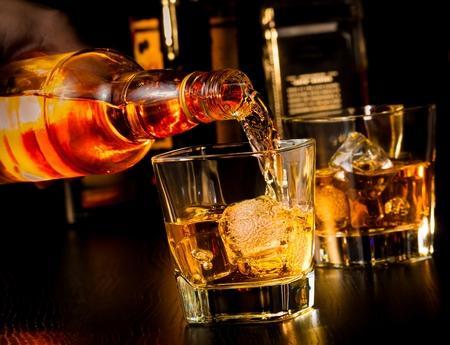 botella de whisky: camarero vierte el whisky delante de whisky de cristal y botellas en la mesa de madera