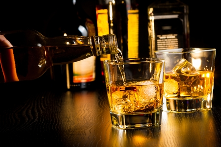 barman: barman pouring whiskey in front of bottles on wood table, focus on top of bottle