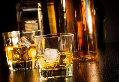 botella de whisky: dos vasos de whisky delante de las botellas en la mesa de madera Foto de archivo
