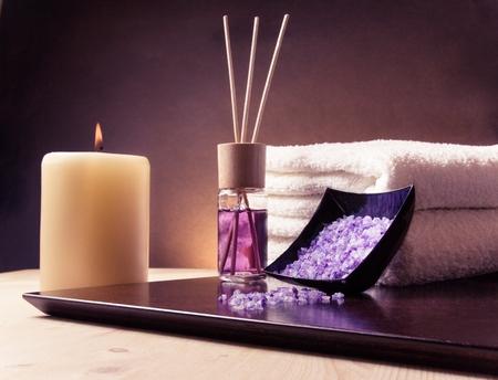 スパ積み上げタオルで境界線の背景をマッサージ、ディフューザーと海塩、紫のグラデーション背景の香水