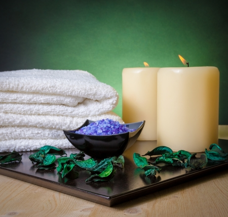 perfumed candle: Spa massage border background with towel stacked, perfumed leaves, candle and sea salt on green gradient background