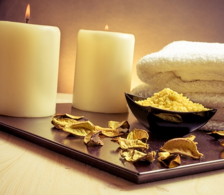 perfumed candle: Spa massage border background with towel stacked, perfumed leaves, candle and sea salt on gold gradient background