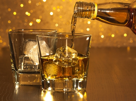 barman pouring whiskey in front of empty whiskey glass on gold bokeh