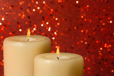 religious holiday: candles with flame on red bokeh background and space for text