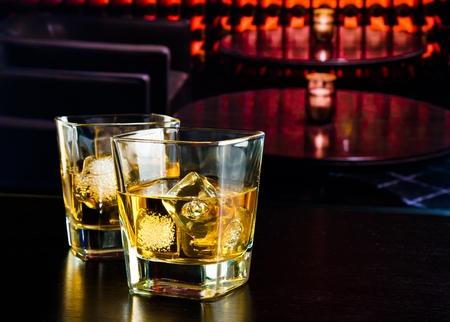 botella de licor: vasos de whisky con hielo en un bar en la mesa de madera