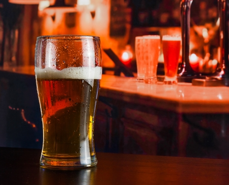 pinta: Glass of fresh beer on wood table in a pub