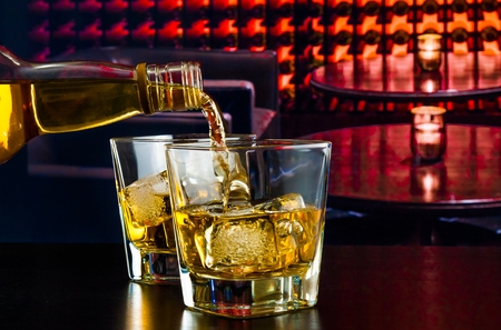 barman pouring whiskey in a lounge bar on wood table