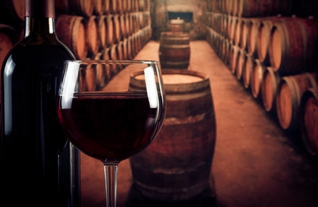 wine glass near bottle in the old wine cellar with barrels with space for text photo