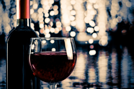 red wine glass near bottle with light bokeh in background photo