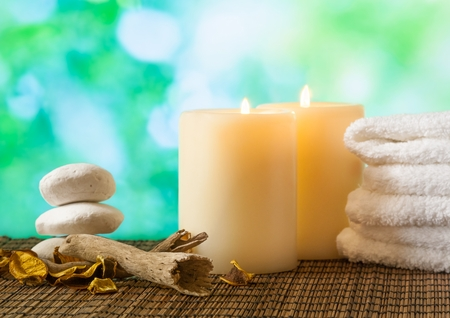 perfumed candle: Spa massage border background with towel stacked, candles and perfumed leaves on green bokeh background