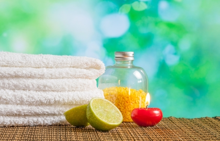 perfumed candle: Spa massage border background with towel stacked,red candle and lime on green bokeh background