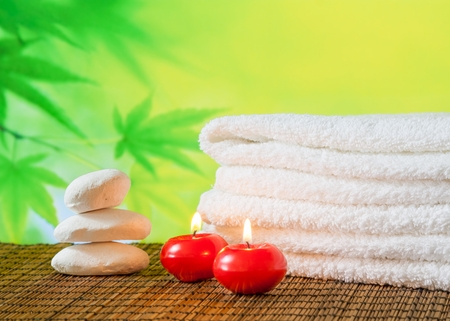 perfumed candle: Spa massage border background with towel stacked,red candles and stone on green background