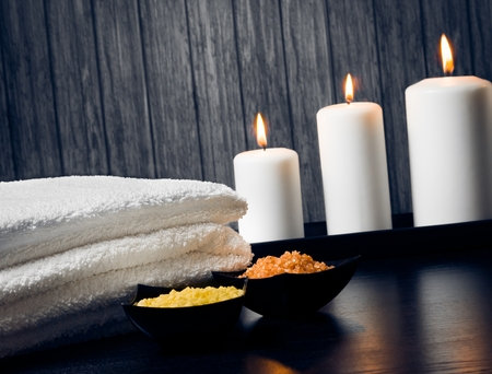 perfumed candle: Spa massage border background with towel stacked,candles and sea salt on wood background