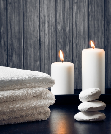 Spa massage border background with towel stacked,candles and stone on wood background photo