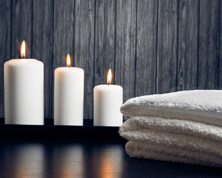 perfumed candle: Spa massage border background with towel stacked and candles on wood background