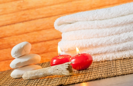 perfumed candle: Spa massage border background with towel stacked stone and red candles on wood background