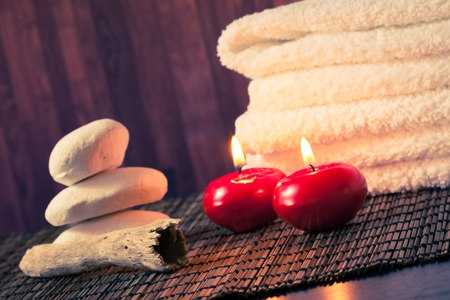 Spa massage border background with towel stacked stone and red candles on wood background warm atmosphere photo