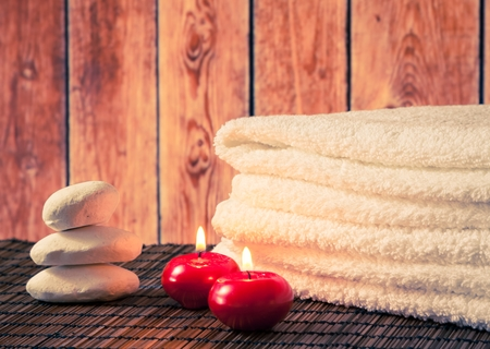 perfumed candle: Spa massage border background with towel stacked stone and red candles on wood background warm atmosphere Stock Photo
