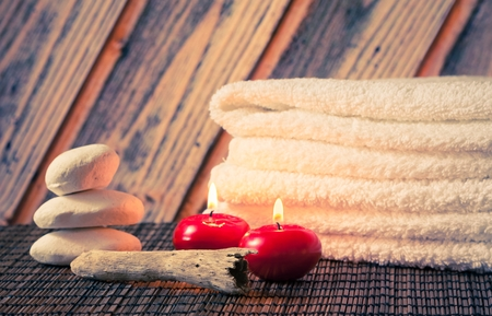 Spa massage border background with towel stacked stone and red candles on wood background photo