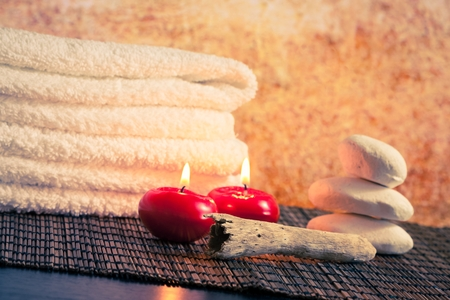 perfumed candle: Spa massage border background with towel stacked stone and red candles on wood table Stock Photo