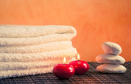 perfumed candle: Spa massage border background with towel stacked stone and red candles on bamboo table