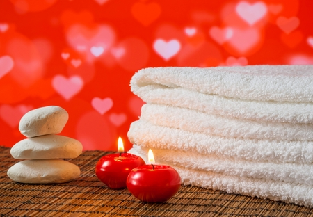 Spa massage border with towel stacked,red candles and stone on hearths decoration background for valentine day Stock fotó