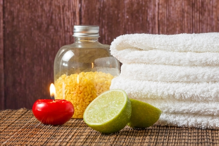 perfumed candle: Spa massage border background with towel stacked red candle and lime on wood background Stock Photo