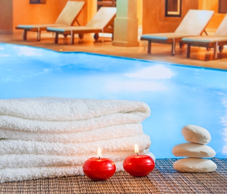 perfumed candle: Spa massage border background with towel stacked,red candles and stone on swimming pool background